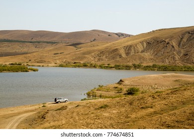 SUV on the shore of the lake against the backdrop of the hills