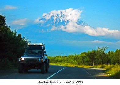 SUV rides on the asphalt road against the background of a large volcano