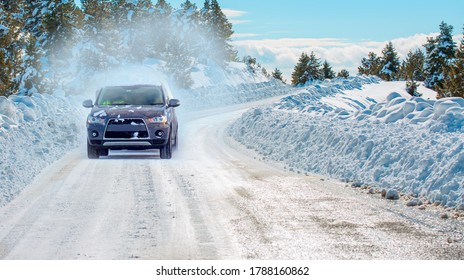 SUV rides on a winter forest road - A car in a snow-covered road among trees and snow hills