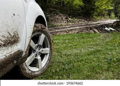 SUV wheel closeup in a countryside landscape with a muddy road and grass