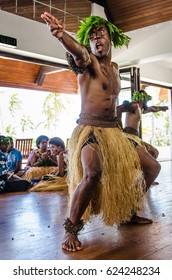 SUVA, FIJI - OCTOBER, 24, 2016: Indigenous male dancers decorated as warriors and dressed in grass skirts perform a traditional dance in front of tourists staying at a beach resort.
