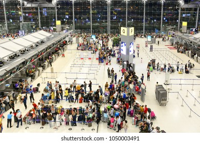 Suvarnabhumi Airport, Bangkok, Thailand - March 1, 2018 : crowd of passengers in row wait for checking-in at airlines counter in airport departure terminal hall, this is the main airport of Thailand