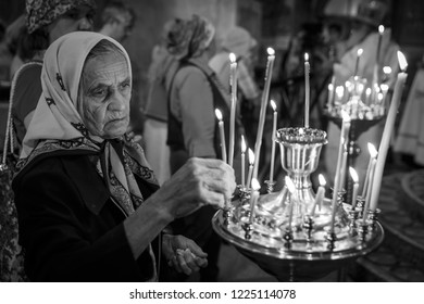 Suzdal, Russia - August 19, 2014: An elderly woman puts a candle in a Russian Orthodox church.