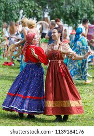 Suzdal, Russia - August 19, 2016: Folk festivities dedicated to the Harvest Festival. Two women in traditional Russian sundresses are dancing.