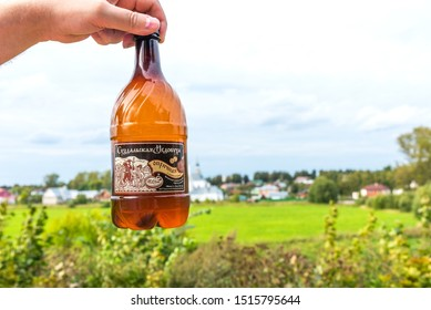 Suzdal, Russia - august, 24 2019: Suzdal Mead on the background of a rural landscape. Traditional Russian souvenir in Suzdal. Traditional alcoholic drink in Suzdal, Russia.