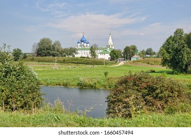 SUZDAL, RUSSIA - Beautiful landscape of Suzdal with the view from high bank of River Kamenka at Pushkarskaya Street on the river and people walking to the architectural ensemble of Suzdal Kremlin.