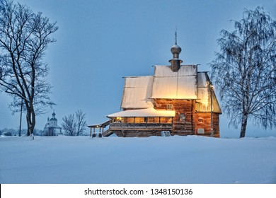 SUZDAL, RUSSIA - Beautiful winter landscape of Suzdal with a view of the old wooden church of St. Nicholas on the grounds of Suzdal's Kremlin framed by trees in the twilight during snowfall.