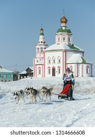 Suzdal, Russia - February 24, 2018: Dog sled racing. A woman is driving a husky dog team.
