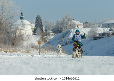 Suzdal, Russia - February 24, 2018: Dog sled racing. Woman with racing dogs on a snowy track.