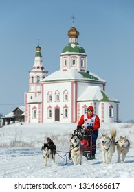 Suzdal, Russia - February 24, 2018: Dog sled racing. A man on a sleigh harnessed by dogs.