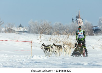 Suzdal, Russia - February 24, 2018: Dog sled racing. A musher controls a sleigh drawn by dogs husky.