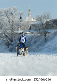 Suzdal, Russia - February 24, 2018: Dog sled racing. Woman on a sleigh with two racing dogs.