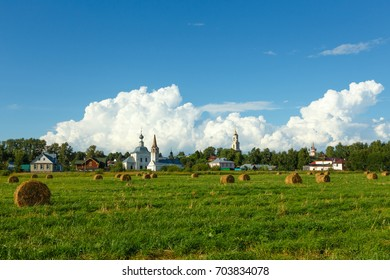 Suzdal, Russia. Field with haystacks, old temples and beautiful clouds in the sky.