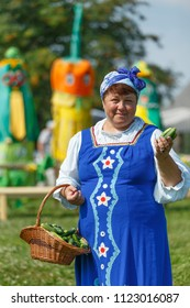 Suzdal, Russia - July 16, 2016: The Cucumber Festival. The saleswoman offers to buy cucumbers.