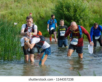 Suzdal, Russia - July 22, 2018: Golden ring ultra trail. The guy refreshes the girl with water during the river crossing.