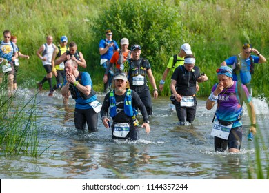 Suzdal, Russia - July 22, 2018: Golden ring ultra trail. Athletes of the ultra marathon race crossing the river.