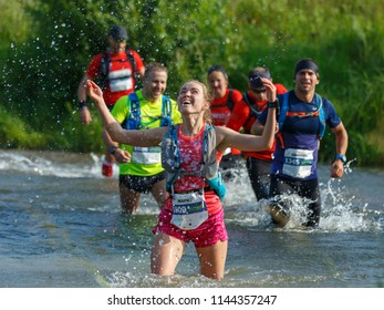 Suzdal, Russia - July 22, 2018: Golden ring ultra trail. A happy young girl is raising water splashes upwards by crossing a river into a ford.
