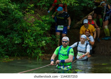 Suzdal, Russia - July 22, 2018: Golden ring ultra trail. A group of athletes cross the river to the ford.