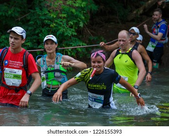 Suzdal, Russia - July 22, 2018: Golden ring ultra trail. A woman with a gel tube in her teeth overtakes the athletes during crossing the river.