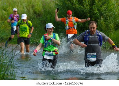 Suzdal, Russia - July 22, 2018: Golden ring ultra trail. A man overtakes a woman during the crossing of a river.