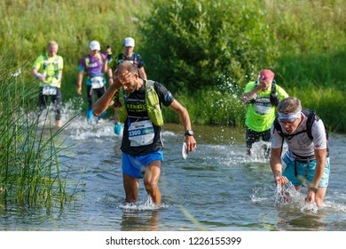 Suzdal, Russia - July 22, 2018: Golden ring ultra trail. Runners overcome ford on the river.