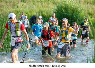 Suzdal, Russia - July 22, 2018: Golden ring ultra trail. A man helps a young girl to cross the river.