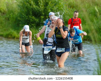 Suzdal, Russia - July 22, 2018: Golden ring ultra trail. The girl is refreshed by water during the crossing of the river.