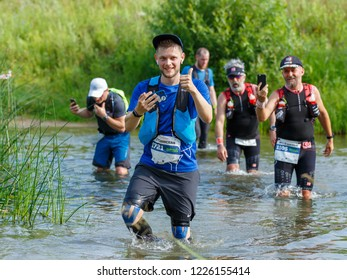 Suzdal, Russia - July 22, 2018: Golden ring ultra trail. A young man shows his thumb up, crossing the river to a ford in the course of a marathon distance.