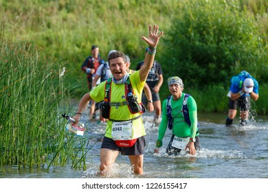 Suzdal, Russia - July 22, 2018: Golden ring ultra trail. A marathon runner crossing the river, greets the fans.