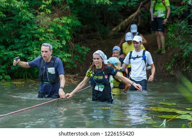 Suzdal, Russia - July 22, 2018: Golden ring ultra trail. A group of marathon runners cross the river to the ford.