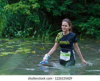 Suzdal, Russia - July 22, 2018: Golden ring ultra trail. Beautiful young girl crosses the river in a ford.