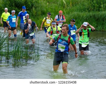 Suzdal, Russia - July 22, 2018: Golden ring ultra trail. A group of marathon runners crossing the river.