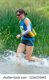 Suzdal, Russia - July 22, 2018: Golden ring ultra trail. A woman is running along the river.