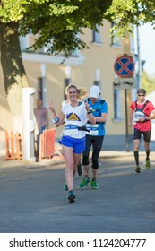 Suzdal, Russia - July 23, 2017: Golden Ring Ultra Trail. Happy girl running in the street and shows a sign of victory.