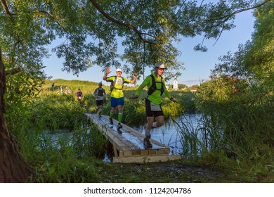 Suzdal, Russia - July 23, 2017: Golden Ring Ultra Trail. Cross-country runners cross a small stream along a wooden bridge.