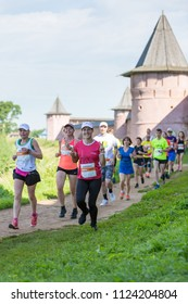 Suzdal, Russia - July 23, 2017: Golden Ring Ultra Trail. People running on dirt path along the monastery wall. Woman shows a sign of victory.