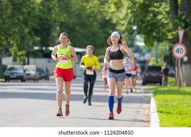 Suzdal, Russia - July 23, 2017: Golden Ring Ultra Trail. Girl runs down the street and shows a sign of victory.