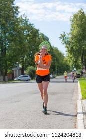 Suzdal, Russia - July 23, 2017: Golden Ring Ultra Trail. A Russian girl with a kokoshnik runs along the city street.