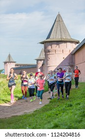 Suzdal, Russia - July 23, 2017: Golden Ring Ultra Trail. People running on dirt path along the monastery wall.