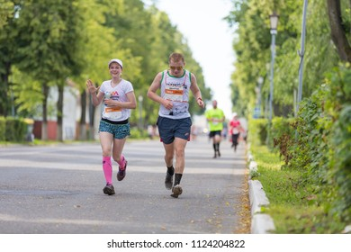 Suzdal, Russia - July 23, 2017: Golden Ring Ultra Trail. A young girl and a guy are running down the city street.