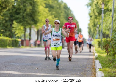 Suzdal, Russia - July 23, 2017: Golden Ring Ultra Trail. Woman runs down the street and shows a sign of victory.