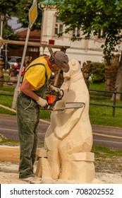 SUZDAL, RUSSIA - JUNE 29, 2017: Artist creating the wooden sculpture of Homunculus loxodontus. Chainsaw carving festival. Documentary editorial