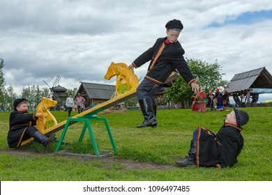 Suzdal, Russia - June 4, 2017: Folk festivities dedicated to the feast of the Holy Trinity in Suzdal. The boys are playing on the swings.