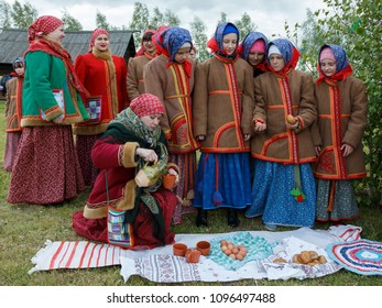 Suzdal, Russia - June 4, 2017: Folk festivities dedicated to the feast of the Holy Trinity in Suzdal. Woman gives food and drink to children.