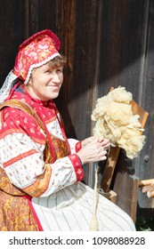 Suzdal, Russia - June 4, 2017: Folk festivities dedicated to the feast of the Holy Trinity in Suzdal. Woman spinning yarn.