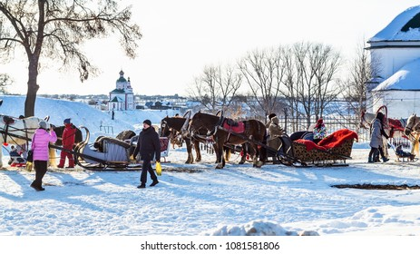 SUZDAL, RUSSIA - MARCH 9, 2018: tourists near horse sledges in near Church of St. Paraskeva or Pyatnitskaya Church and view of Church of Elijah the Prophet on Ivanovo Hill (Elijah Church) in winter