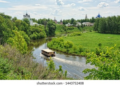 SUZDAL, RUSSIA - Spring cityscape of Suzdal from the high bank of Kamenka river with churches and a tourist boat floating dawn at the curve of the river.