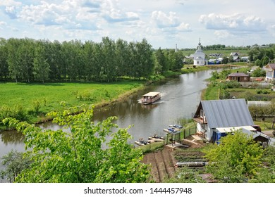 SUZDAL, RUSSIA - Spring cityscape of Suzdal with the view from the high bank of Kamenka river with a sightseeing boat floating at the curves of the river.