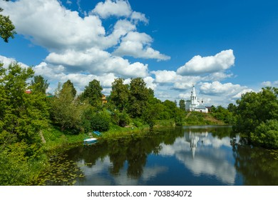 Suzdal, Russia. Summer landscape with river, temple on the hill and beautiful clouds in the sky