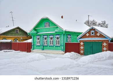 SUZDAL, VLADIMIR REGION, RUSSIA - Covered snow the bright green wooden Russian house with garage on Pushkarskaya street with elements of decoration in old style.